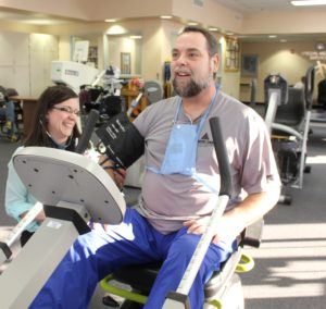 Smiling doctor takes elderly patient's blood pressure while riding a stationary bike