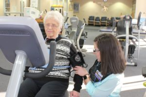 Doctor takes an elderly patients blood pressure on a stationary bike