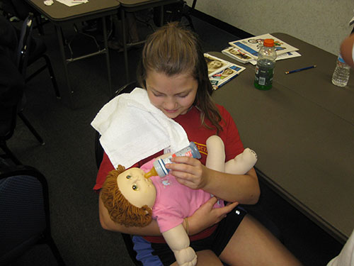 Child bottle feeds a doll