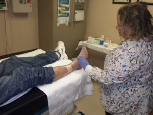 Barb helping a patient with his foot